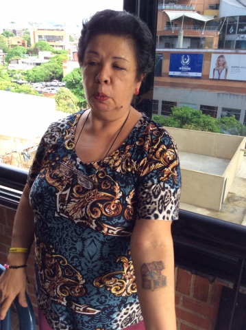 Baruta UBCh militant, a retired nurse, displays her tattoo of Chavez's heart. She had the tattoo done after his death. (Arlene Eisen)