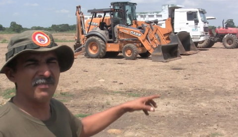 "José Tapia Coirán points to an example of the ubiquitous farming equipment on Hato Santa Rita land, accused of being ""unproductive"" by agribusiness Fedenagas. (Aporrea tvi)"