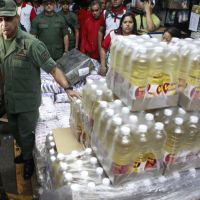 Member of the Venezuelan National Guard stands by a large supply of hoarded cooking oil.  (PHOTO:Venezuelasolidarity)