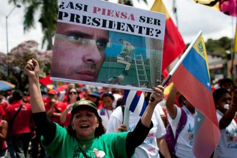 A woman holds a placard reminding people of Capriles' role in the coup in the lead up to presidential elections between Capriles and Chavez, won by Chavez in October, 2012 (EFE)