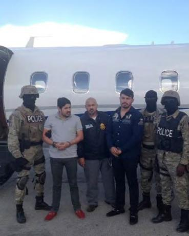 Efrain Antonio Campo Flores (2nd from L) and Franqui Fancisco Flores de Freitas stand with law enforcement officers in this November 12, 2015 photo after their arrest in Port Au Prince, Haiti. (U.S. Attorney's Office Manhattan)