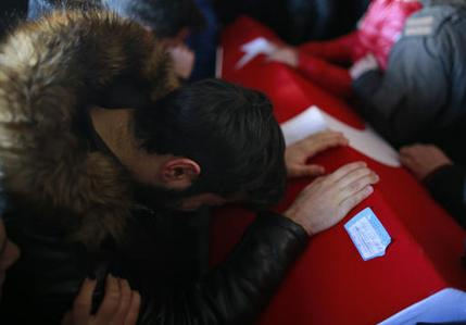 A mourner cries over the Turkish flag-draped coffin of Yunus Gormek, 23, one of the victims of the NYD attack (Associated Press/Emrah Gurel)