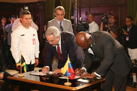 Venezuelan Oil Minister Nelson Martinez and Jamaican Minister for Science, Energy and Technology Andrew Wheatley sign the much awaited agreement in Caracas. (PrensaPresidencial)
