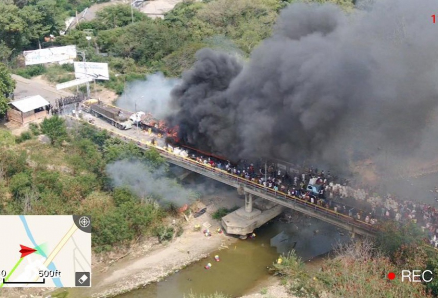 "A truck allegedly carrying ""aid"" from USAID is set on fire halfway across the Simon Bolivar international bridge connecting Venezuela and Colombia February 23, 2019, The Venezuelan National Guard piquet can be observed in the top left of the image, and the multitude of protesters stemming from the Colombian side coming from the bottom right (Courtesy)"