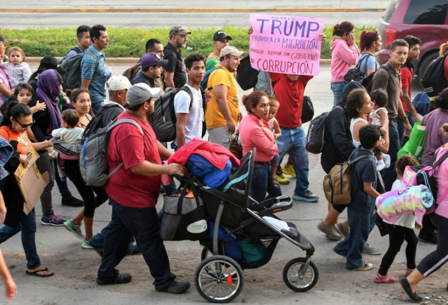 'Trump provokes migration because he supports a corrupt government' read the placard by the migrants. (AFP)