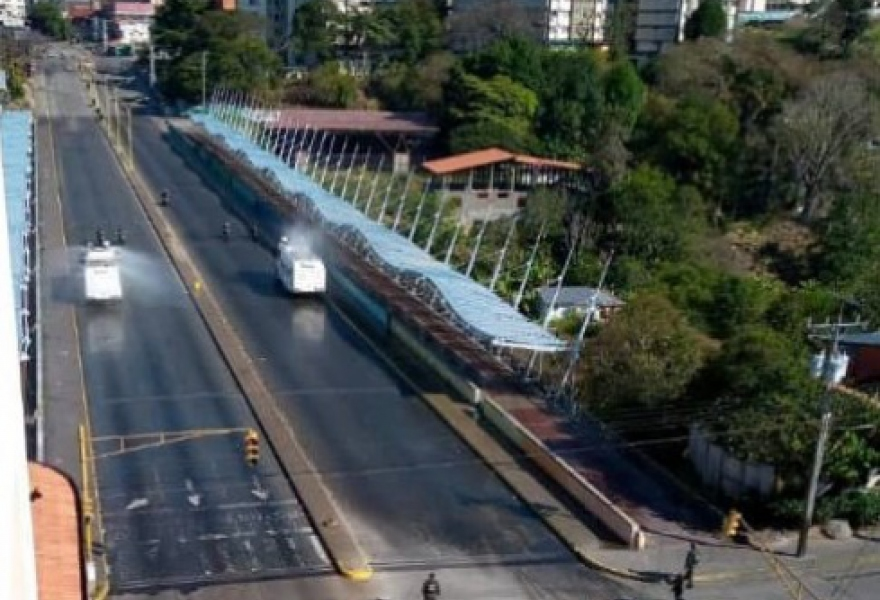 Two sanitary vehicles donated by the central government clean the main bridge in Merida City, Merida State on Sunday. (Juan Carlos Uzcagetui)