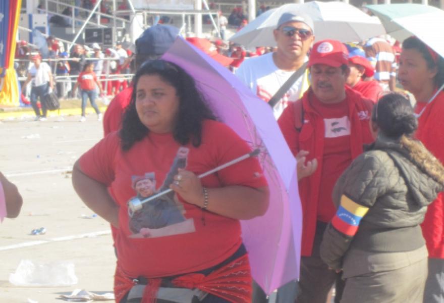 A woman queuing and shading herself from the sun (Ewan Robertson / Venezuelanalysis.com)