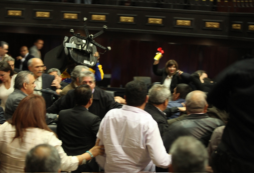 One opposition lawmaker throws a chair towards Chavista lawmakers, while another opposition legislator sounds an air horn. (AVN)