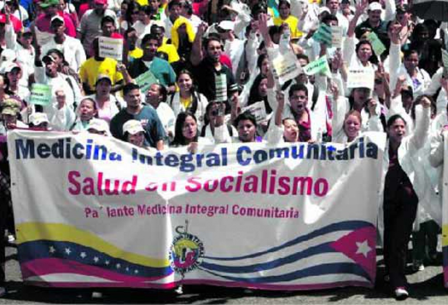 "Students and graduates of comprehensive community medicine on a celebratory march in Caracas. The banner features the Cuban and Venezuelan flags, and reads, ""healthcare in socialism"" (Jesús Contreras)"