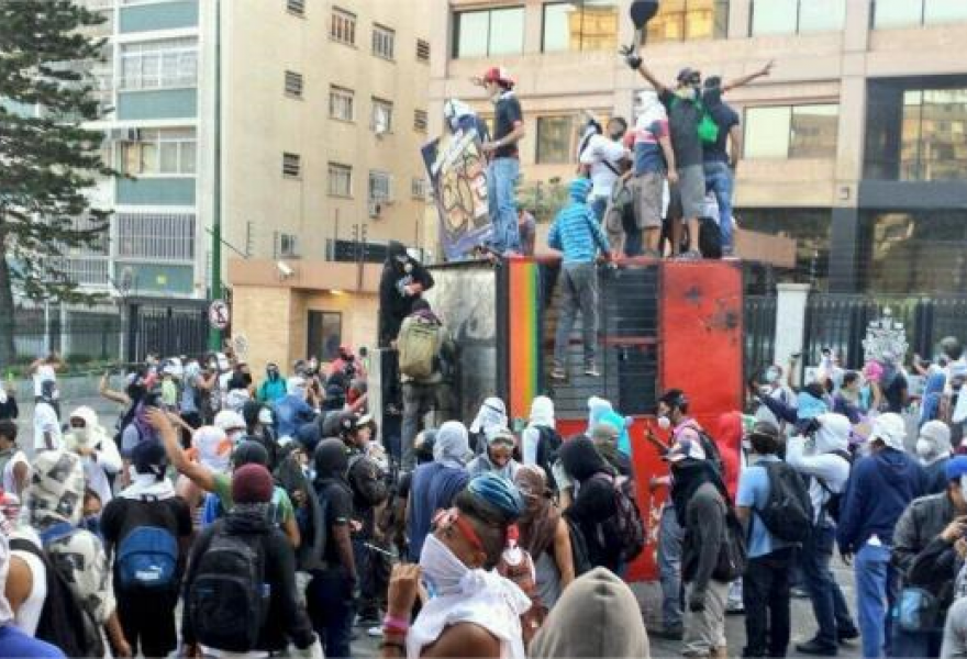 Opposition hardliners destroy a Caracas metrobus ticket booth in Altamira on Sunday (twitter)