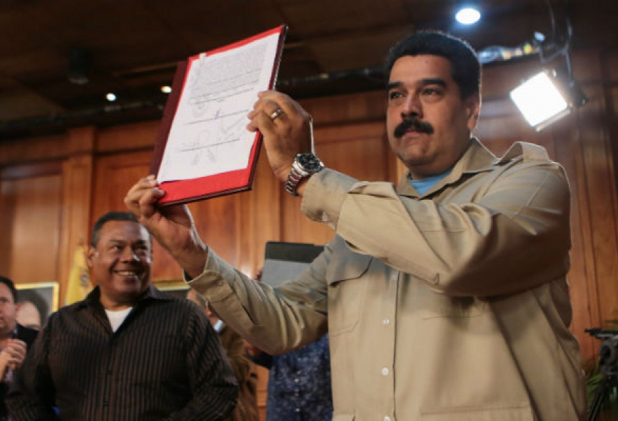 Nicolas Maduro signs and presents the act which will open discussion for public administrative workers' collective contracts. (Miraflores Press)
