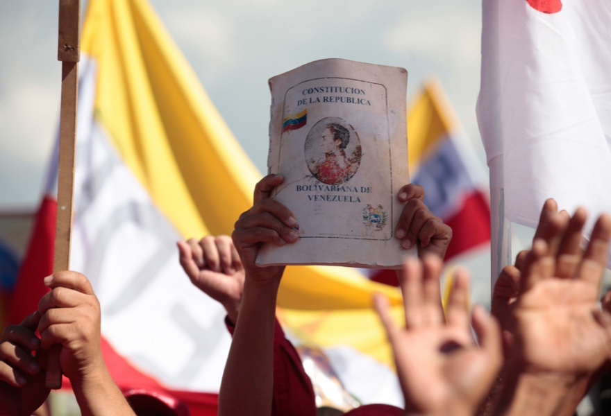 A demonstrator holds up a battered copy of the Constitution of the Bolivarian Republic of Venezuela at the march in Caracas today (prensa Miraflores)