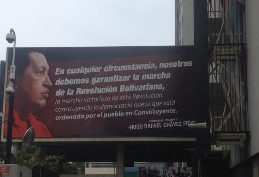 "The Chavez quote reads: ""Under all circumstances, we must guarantee the march of the Bolivarian Revolution... building the new democracy ordained by the people in the the Constituent [Assembly]."" Monica Salterin, pointing to the billboard of outside the Ministry building, told venezuelanalysis.com ""We are here because of these words: We cannot allow all the work we've accomplished in the last 14 years to be lost. We are ready to guarantee the forward march of the Revolution if the government cannot."" (Photo: Lucas Koerner)"