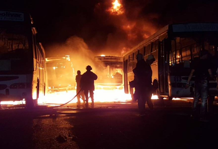 Firefighters attempt to extinguish the fires that destroyed 51 public buses in Bolivar state early Monday morning in another anti-government arson attack. (@TransBolivar)
